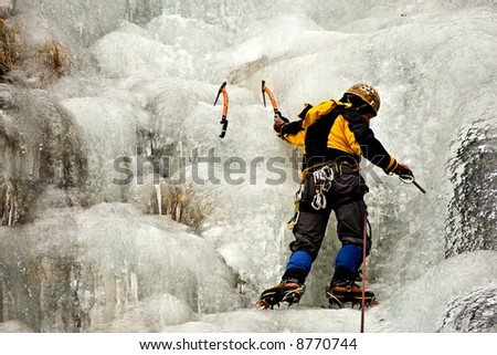 Climber drills a hole in a frozen waterfall