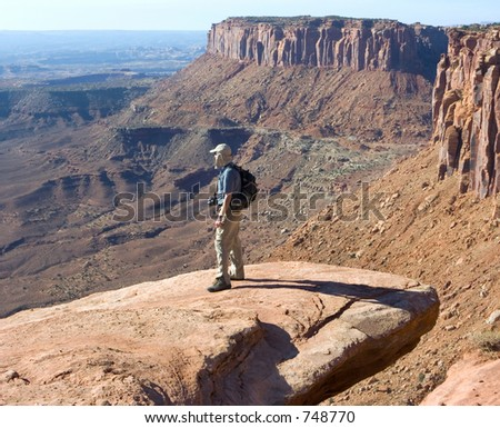 Climber finds a high perch from which to take a photo; Canyonlands, Utah