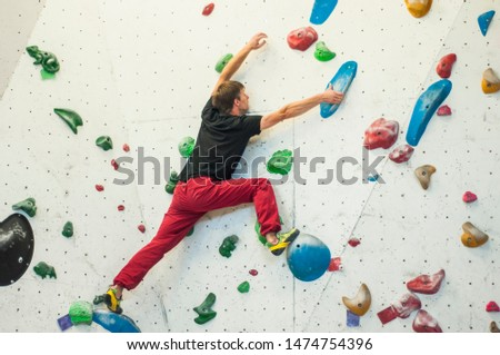 Climber in a boulder gym. Man climbing bouldering problem. Colorful volumes and holds on a white wall. ストックフォト ©