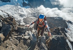 Climber in a safety helmet, harness with backpack ascending a rock wall with Bionnassay Glacier on background and looking at the summit during Mont Blanc ascending,France route.Active climbing concept