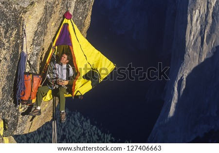 Climber in his hanging camp sleeps on the side of a mountain.