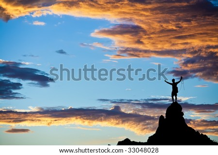 Climber  is silhouetted on the summit of a rock spire in the Sierra Nevada Mountains, California, on a summer day.