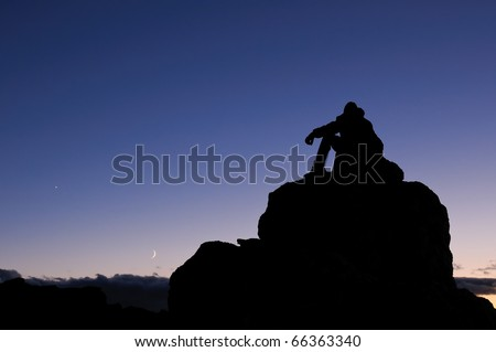 Climber on a mountain peak in the Rocky Mountains of Colorado, under a night sky.