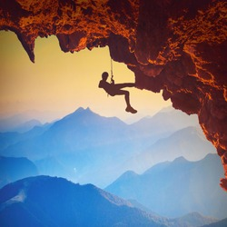 Climber on a rocky cliff in a mountain valley at sunset. Extreme sport.