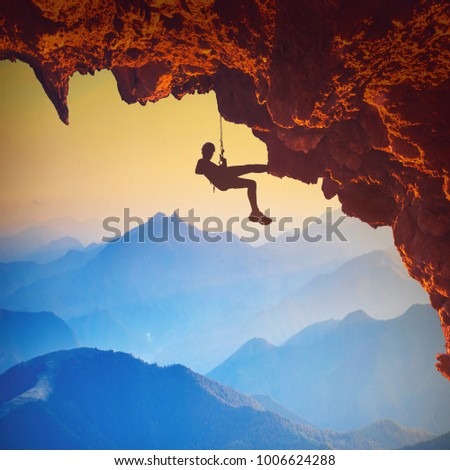 climber on a rocky cliff in a...