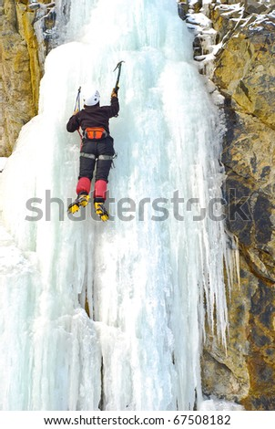 climber on icy waterfall - stock photo