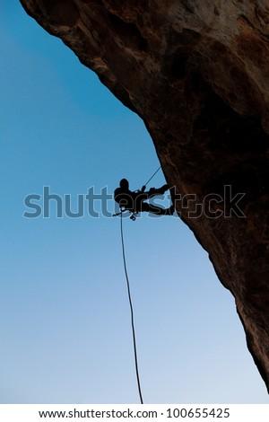 Climber on the rock against the blue sky