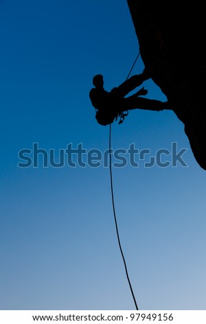 Climber on the rock against the blue sky