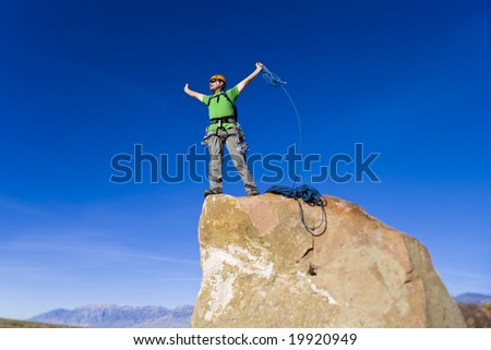 Climber on the summit of a rock spire in the Sierra Nevada Mountains, California, on a sunny day.