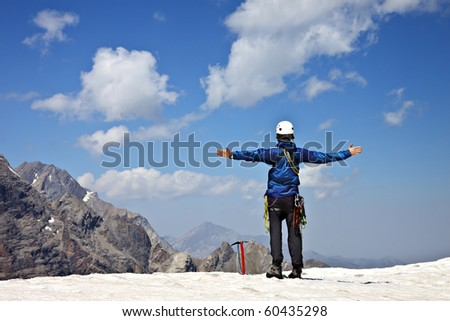 Climber on the top of the snowy mountain enjoy sunny day