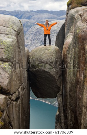 climber on top of rock near sea