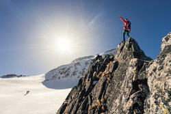 Climber or alpinist at the top of a mountain. A success of mountaineer reaching the summit. Outdoor adventure sports in winter alpine moutain landscape. Sunny day and a climber on a top of a peak.