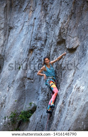Climber overcomes challenging climbing route. A girl climbs a rock. Woman engaged in extreme sport. Extreme hobby. #1416148790