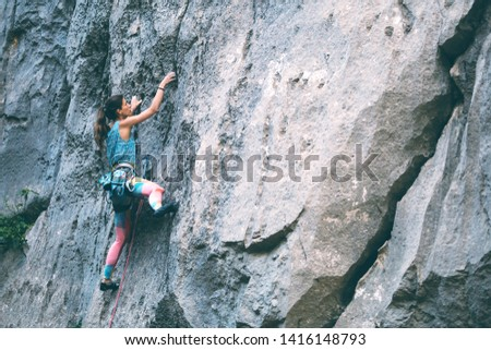 Climber overcomes challenging climbing route. A girl climbs a rock. Woman engaged in extreme sport. Extreme hobby. #1416148793