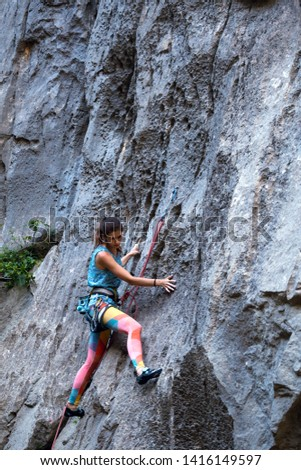 Climber overcomes challenging climbing route. A girl climbs a rock. Woman engaged in extreme sport. Extreme hobby. #1416149597