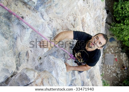 Climber overpassing a difficult part in the wall while rock climbing in Phi Phi Islands, Thailand