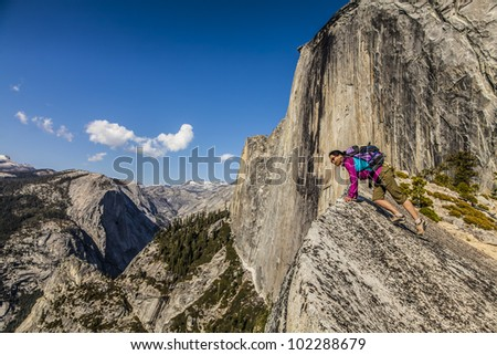 Climber peers over the edge of an abyss in Yosemite National Park,