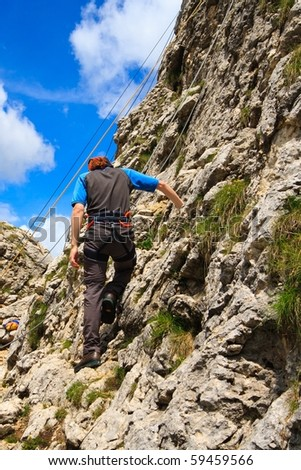 Climber preparing to climb steep rocks in Dolomites