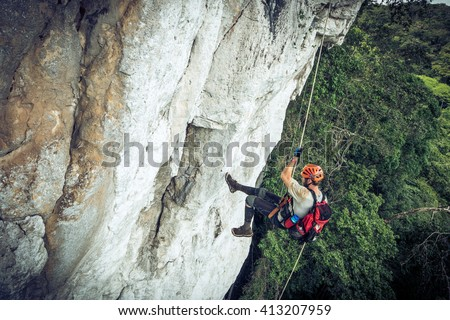Climber rappelling down cliff with helmet and backpack. Photo stock ©