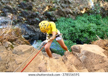 Climber rappelling on forested mountain slope with the evergreen conifers in a scenic summer landscape view. Photo stock ©