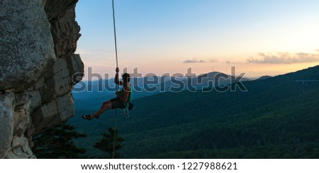 Climber rappels from a beautiful cliff with the Blue Ridge Parkway in the background at sunset Photo stock ©