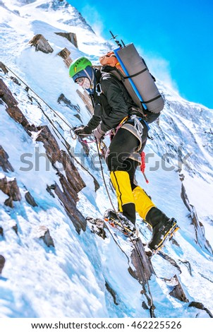 Climber reaches the summit of mountain peak. Climbing and mountaineering sport concept #462225526