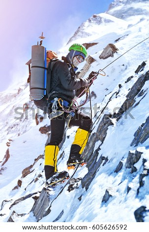 Climber reaches the summit of mountain peak. Climbing and mountaineering sport concept #605626592