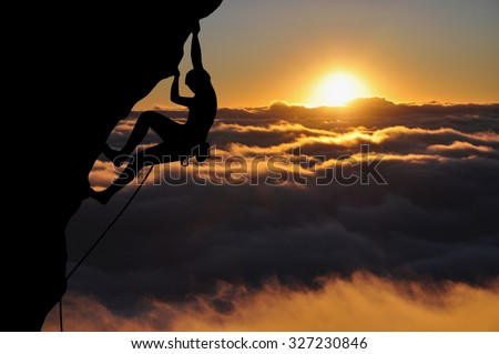 Climber silhouette high above clouds and mountains. Young woman climbing top rope during sunset.