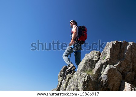 Climber standing on a stone at the top of his route, over a deep blue sky.