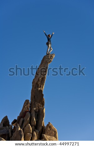 Climber stands on the edge of a rock pinnacle in the remote Mojave Desert of California.