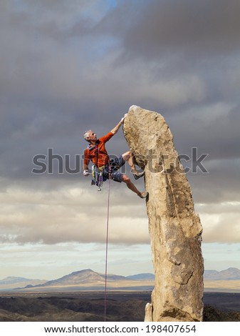 Climber struggles for his next grip on the edge of a challenging cliff