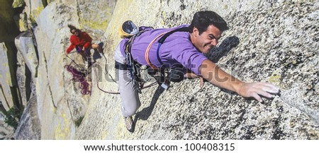 Climber struggles to reach his next grip on a challenging cliff.