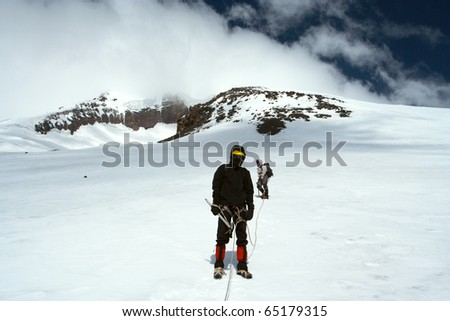 climber walking up by the snowfield to the high summit