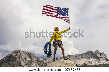 Climber waves an American Flag from the summit after a challenging ascent.
