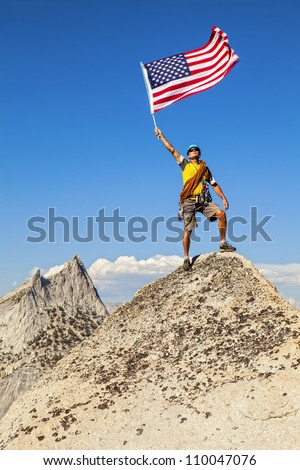 Climber waves an American Flag on the summit after a successful ascent.