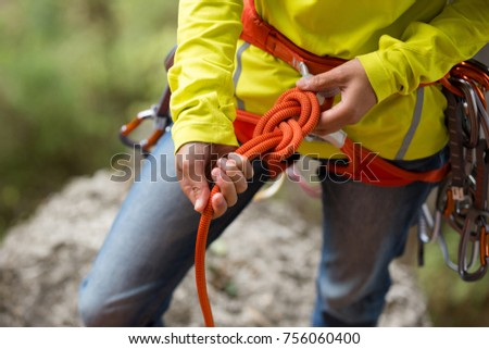 Shutterstock climber wearing safety harness making a eight rope knot
