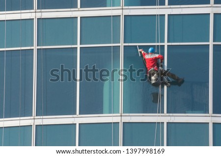 Climber - window cleaner perform the work at wall of an office building #1397998169