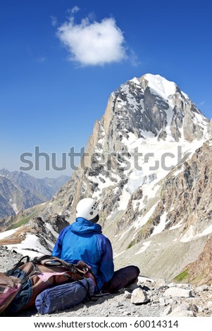 Climber with a backpack looking at the high mountain peak