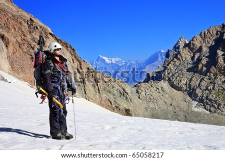 Climber with climbing equipment on the snowy mountain