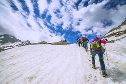 climbers climbing mountain with snow field