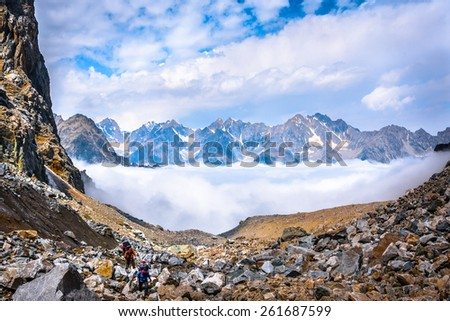 Climbers move above the clouds on background of beautiful mountains. Picture was taken during trekking hike in the majestic and stunning mountains of Caucasia, Bezengi region,Kabardino-Balkaria,Russia