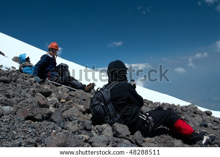 climbers sitting on a mountain summit and looking at the great panoramic view