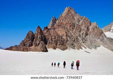 climbers walk up to the top of the mountain
