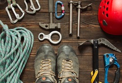 climbing equipment: blue rope, red helmet, hammer, trekking shoes and other set  on dark wooden background, top view