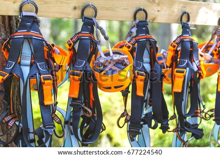 Climbing gear equipment - orange helmet harness zip line safety equipment hanging on a board. Tourist summer time adventure park family and company team building concept for extreme recreation sports #677224540