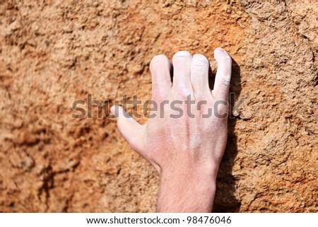 Climbing hand closeup grip during rock climbing. Male hand with chalk powder on rocks.