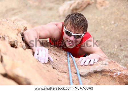 Climbing. Male climber rock climbing cliff wall with climb rope. Strong man climber on the way to summit at success.