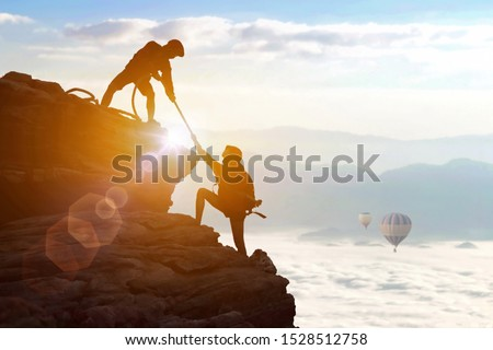 Climbing team are on the climb to the cliff,hiking and team work concept.    Mountaineer climbing a steep cliff.