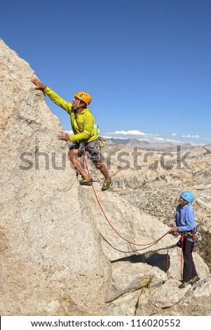 Climbing team ascending a challenging cliff.