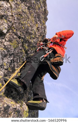 Climbing team leader searching the rack for a protection piece